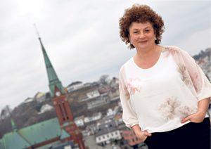 BYENS TAK:Her Står Kristin Ytterst I Hagen Hjemme På Nesheia Med Byens Tak Som Utsikt.
