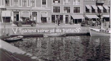"""KRIGSMINNER: """"V"""" og """"Tyskland seirer på alle fronter"""" ble ofte malt i gult på bygninger og gjerder rundt om i hele landet. Her er teksten malt på murkanten i Pollen i Arendal. Bildet er hentet fra AKHF.no"""