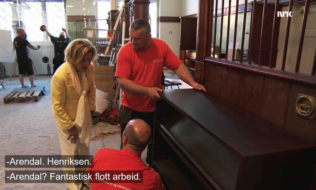 KONGELIG ROS: Dronning Sonja skryter av snekkerarbeidet Jaroslaw Mrozik og Piotr Wieder ved Henriksen Snekkeri har vært med å utføre. Foto: skjermbilde fra NRK.no