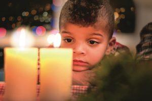 Sad Boy Beside Christmas Candles.
